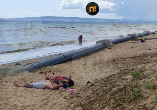 На крымском пляже люди отдыхают рядом с канализационной трубой